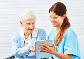 female caregiver showing documents to her old woman patient