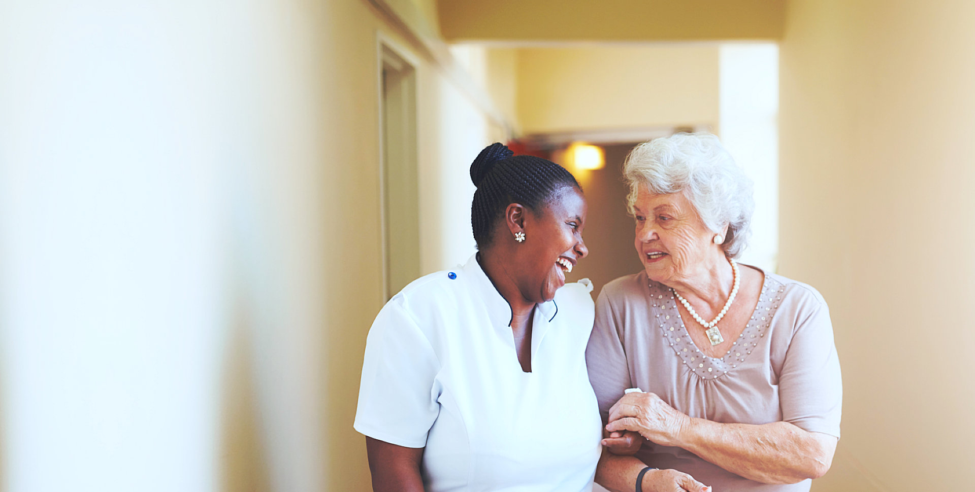 african female caregiver and her old woman patient walking in the hospital hallway