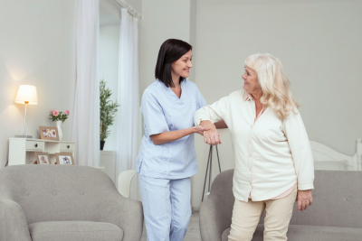 female caregiver assisting to her old woman patient while smiling to each other