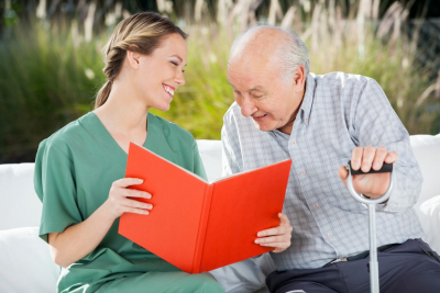 female caregiver and her old man patient reading documents while smiling