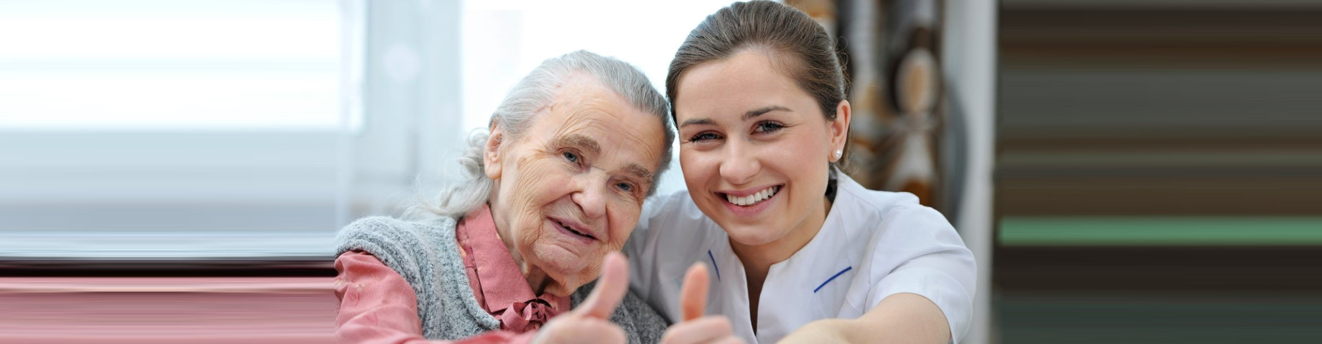 female caregiver and her old woman patient doing thumbs up