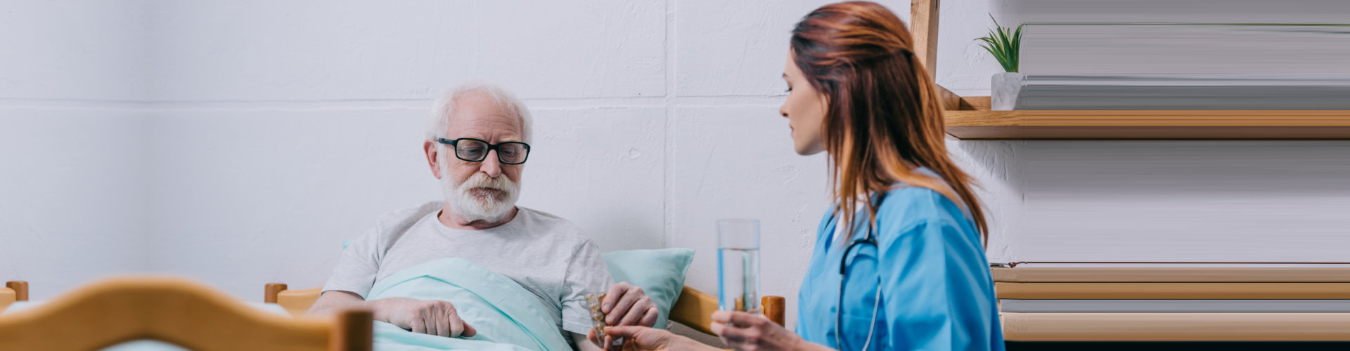 female caregiver giving medicine to her old man patient